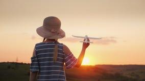 Девушка с отрезками провода и шляпа играя с деревянным самолетом на заходе солнца Мечта международного перемещения концепция стоковые изображения rf