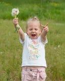 Девушка с одуванчиками на предпосылке травы Стоковое Изображение