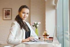 Девушка с пересеченными руками на таблице сидя около компьтер-книжки стоковые изображения