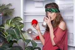 Девушка с питьевым молоком вьющиеся волосы Держатель женщины нося держа красные яблоко, витамины и концепцию здоровья Дама внутри Стоковые Фотографии RF