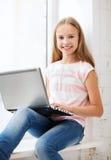 Девушка с ПК компьтер-книжки на школе Стоковое Изображение