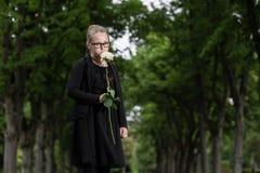 Девушка с покойницами белой розы оплакивая на погосте Стоковая Фотография RF