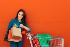 Девушка с покупками и сумки подарка перед магазином супермаркета Стоковое фото RF
