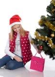 Девушка с подарками приближает к рождественской елке Стоковые Изображения