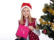 Девушка с подарками приближает к рождественской елке Стоковые Фотографии RF