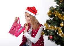 Девушка с подарками приближает к рождественской елке Стоковая Фотография RF
