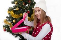 Девушка с подарками приближает к рождественской елке Стоковое Изображение