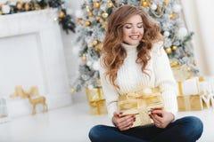 Девушка с подарком рождества около красивой одетой рождественской елки Стоковая Фотография