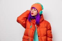 Девушка с пурпурными волосами в куртке с наушниками стоковое фото rf