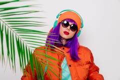 Девушка с пурпурными волосами в куртке с наушниками стоковое изображение