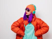 Девушка с пурпурными волосами в куртке с наушниками стоковое фото