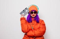 Девушка с пурпурными волосами с наушниками и VHS стоковые фото