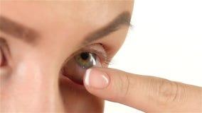 Девушка с плохим зрением кладет объектив и вспышки конец вверх Белая предпосылка движение медленное видеоматериал