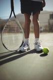 Девушка с ракеткой тенниса и шарик на суде Стоковые Фото