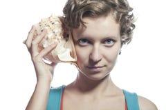 Девушка с раковиной моря к вашему уху Стоковая Фотография