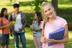 Девушка с друзьями коллежа в предпосылке на кампусе Стоковое фото RF