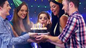Девушка с друзьями празднует день рождения и дует вне свечи на торте 4K сток-видео