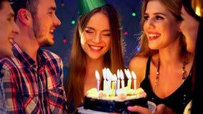 Девушка с друзьями празднует день рождения и дует вне свечи на торте 4K видеоматериал