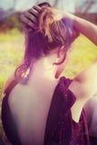 Девушка с руками в взгляде задней части волос внешнем в поле Стоковая Фотография RF