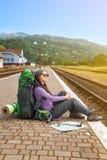 Девушка с рюкзаком и поездом карты ждать на железнодорожном вокзале Стоковая Фотография