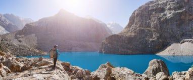 Девушка с рюкзаком около озера большого Alo на backgroun скалистой горы стоковые изображения rf