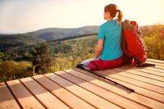 Девушка с рюкзаком сидя и смотря природа, задний взгляд стоковое фото rf