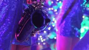 Девушка с саксофоном, музыкальная группа в составе девушки с саксофоном выполняет на этапе, голубом платье, свете этапа, a сток-видео