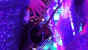 Девушка с саксофоном, музыкальная группа в составе девушки с саксофоном выполняет на этапе, голубом платье, свете этапа, a видеоматериал