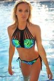 Девушка с светлыми волосами в костюме заплывания, расслабляющем близко плавая po Стоковые Изображения RF