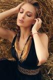 Девушка с светлыми волосами в элегантном платье представляя на сене Стоковые Фото