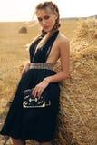 Девушка с светлыми волосами в элегантном платье представляя на сене Стоковая Фотография
