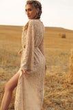 Девушка с светлыми волосами в элегантном платье представляя на сене Стоковое Фото