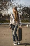 Девушка с скейтбордом на улице Стоковые Изображения RF