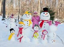 Девушка с снеговиками стоковая фотография rf