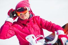 Девушка с сноубордом на снеге Стоковые Изображения