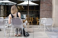 Девушка с собакой сидит на таблице в кафе стоковое изображение