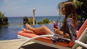 Девушка с стеклом коктеиля близко к бассейну Стоковые Изображения