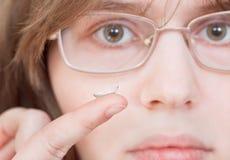 Девушка с стеклами держит контактные линзы Стоковая Фотография