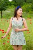 Девушка с стойками синей полосы в поле мака стоковое изображение rf