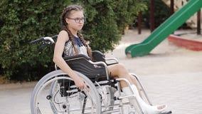 Девушка с сломанной ногой сидит в кресло-коляске перед спортивной площадкой видеоматериал