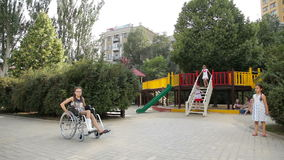 Девушка с сломанной ногой сидит в кресло-коляске перед спортивной площадкой сток-видео