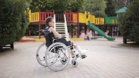 Девушка с сломанной ногой сидит в кресло-коляске перед спортивной площадкой акции видеоматериалы