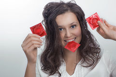 Девушка с с 3 пакетами презерватива красного цвета Стоковая Фотография