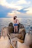 Девушка с татуировкой бабочки дальше подпирает берега залива с бетонными конструкциями Стоковое Фото