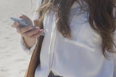 Девушка с телефоном в ее руке стоковые фото