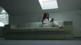 Девушка с телефоном дома на окне видеоматериал