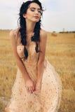Девушка с темными волосами в элегантном платье представляя на сене Стоковое фото RF