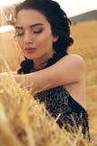 Девушка с темными волосами в элегантном платье представляя на сене Стоковое Изображение RF