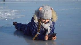 Девушка с телефоном на льде видеоматериал