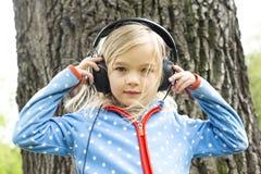 Девушка слушает к музыке на наушниках Стоковое фото RF